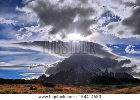 Incredible shaped cloud formed by glaciers glisten in the sun. On the horizon are seen mountains with snow-capped peaks. The Chile National Park
