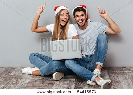 Portrait of happy couple with laptop. sitting down and smiling