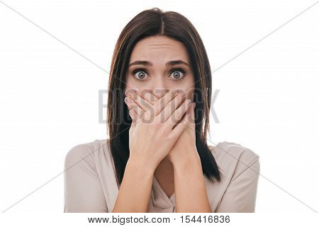 Oh no! Frustrated young woman covering mouth with hands and staring at camera while standing against white background