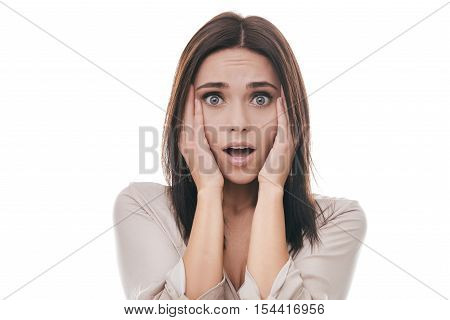 Shocked woman. Frustrated young woman touching face with hands and staring at camera while standing against white background