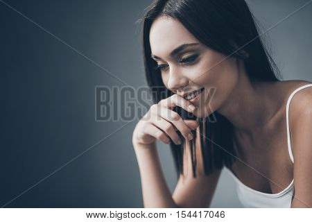 Thinking about good things. Attractive young woman holding hand on chin and looking thoughtful while sitting against grey wall