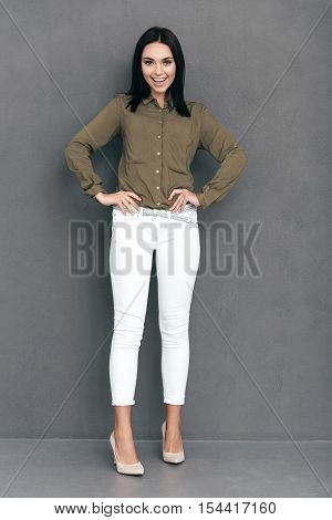 Confident beauty. Full lenght of attractive young woman in smart casual wear posing against grey background and looking happy