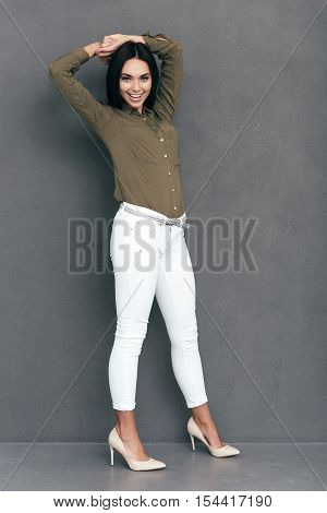 Elegance and beauty. Full lenght of attractive young woman in smart casual wear posing against grey background and looking happy