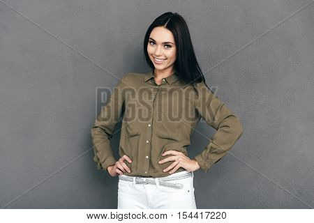 Feeling good and looking great. Happy young woman in smart casual wear standing against grey background and holding hands on hip