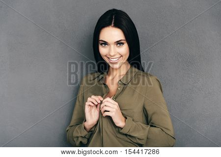 Feeling flirty tonight. Attractive young woman unbuttoning her shirt and looking at camera with smile while standing against grey wall