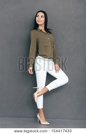 Proud of her new heels. Full lenght of attractive young woman in smart casual wear posing against grey background and looking happy