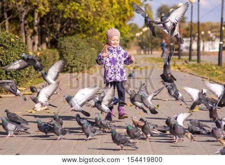 A little girl runs to disperse pigeons