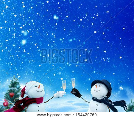 Two funny snowmen celebrating, raising toast.Merry christmas and happy new year greeting card with copy-space.Happy snowmen standing in winter christmas landscape.Snow background
