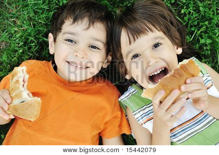 Two cute boys laying on ground in nature and happily eating healthy food