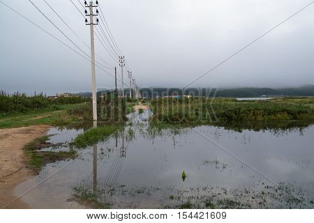 Electric poles are removed to the horizon. Big puddle around them are reflecting the wire and mast.