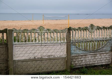 Old-fashioned fence along beach. Fence has intricate decor.