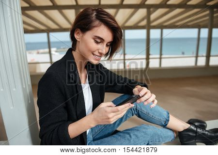 Smiling charming young woman sitting and using mobile phone in arbour on the beach