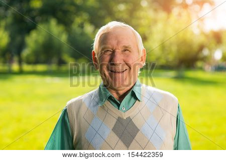 Smile of senior man. Person with gray hair outdoors. Meeting an old friend. Grandpa in good mood.