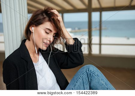 Happy attractive young woman in earphones sitting and relaxing in arbour on seashore