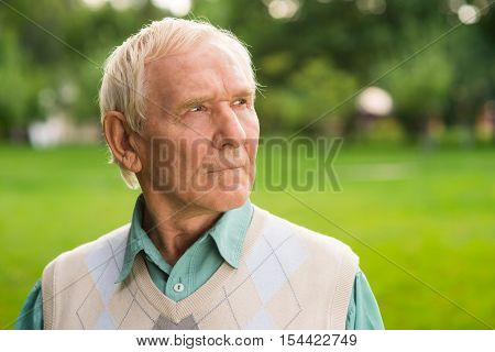Portrait of serious elderly man. Senior male looking to side. Time is merciless. Thinking about victories and losses.