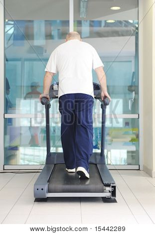 Elderly bald man running in gym