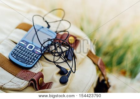 Blue old fashioned smart phone with qwerty keypad and headset on backpack