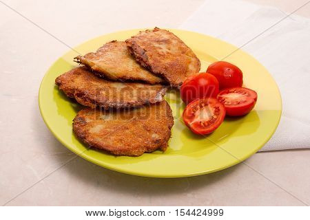 Potato Pancakes With Meat And Tomatoes On Green Plate In Belarusian Style On Light Background..