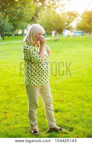 Lady wiping eye with handkerchief. Elderly woman standing on grass. Get through a difficult period. Don't lose your dignity.