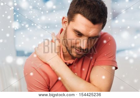 people, healthcare and problem concept - unhappy man suffering from neck pain at home over snow