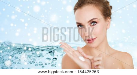 beauty, people, skincare and cosmetics concept - happy young woman with moisturizing cream on hand over water splash bubbles on blue background and snow
