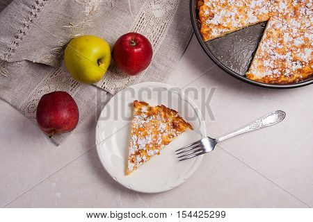 Slice Of Homemade Apple Pie With Fork And Fresh Apples On Light Marble Background