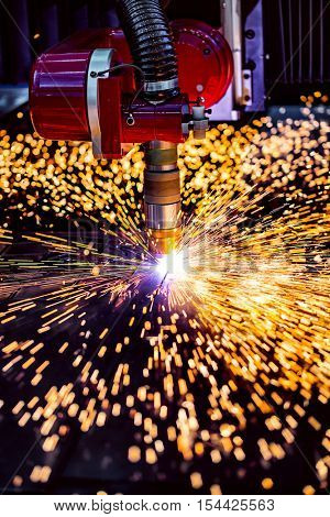 CNC Laser plasma cutting of metal, modern industrial technology. Small depth of field. Warning - authentic shooting in challenging conditions. A little bit grain and maybe blurred.