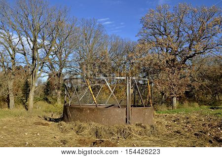 Old cattle feeder with  hay strewn on the ground in a pasture or feedlot
