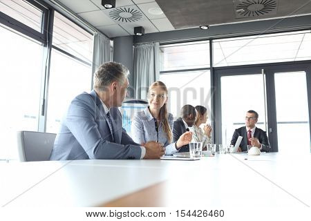 Young businesswoman talking with male colleague in board room