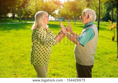 Elderly man and woman outdoor. People touching hands. Solve problems and save feelings. Understanding and mutual respect.