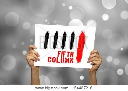 FIFTH COLUMN card in hand with abstract light background. Selective focus