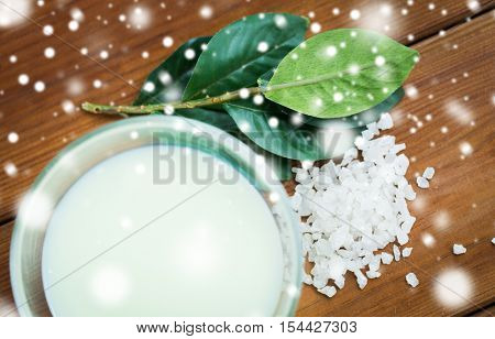 beauty, spa, bodycare, natural cosmetics and wellness concept - close up of body lotion in glass bowl and sea salt on wooden table over snow