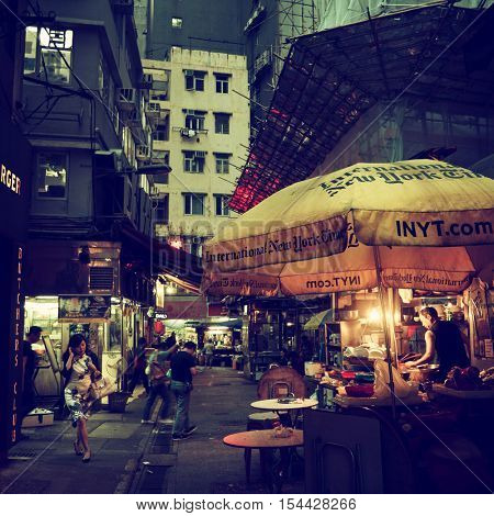 HONG KONG - October 2016: Night street view with people and bistro. Retro look.
