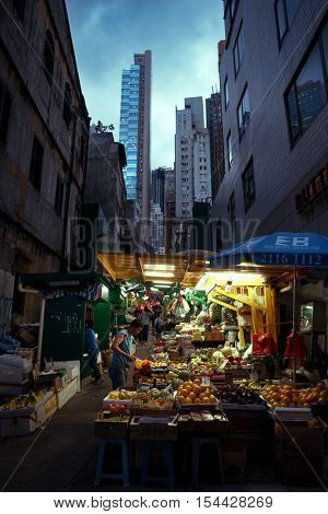 HONG KONG - October 2016: Graham street market with fruit stall, people and skyscrapers in background at night.