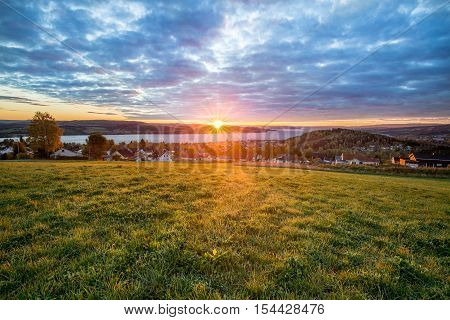 Warm fall Sunrise of cloudy sky in Norway A lovely sunrise picture taken with the view of the Norwegian city called Gjøvik. On the right in the picture  you have the local alpine ski hill