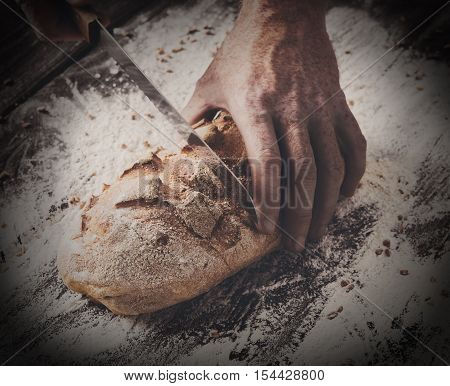 Baking and cooking concept background. Hands of baker closeup cutting bread loaf with knife on rustic wooden table sprinkled with flour. Stained dirty hands of baker, filtered toned image