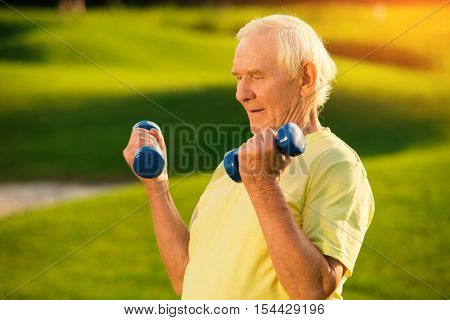 Old man with dumbbells. Person doing exercise outdoor. Strengthen the muscles. Your health is priceless.