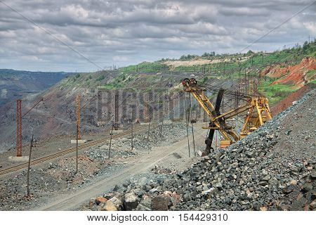View to the iron ore opencast with excavator road and railway track for transporting ore from the quarry