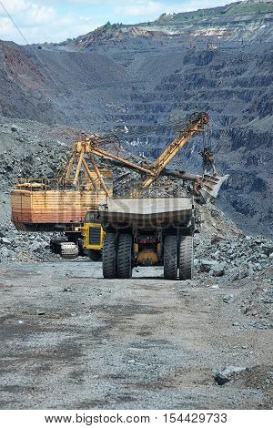 Heavy dump trucks being loaded with iron ore on the opencast by the excavator