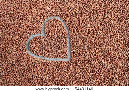 Texture background from buckwheat. Heart from buckwheat. Overhead view