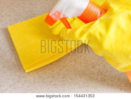 Hand in rubber glove cleans a new kitchen. Woman with housework cleaning the kitchen.