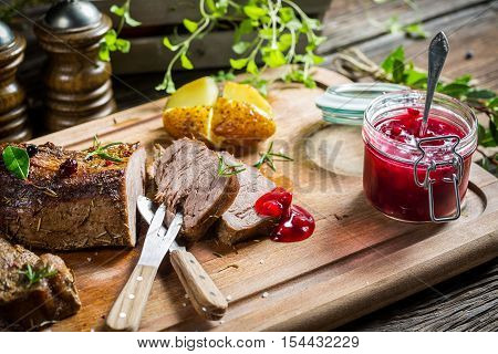 Venison with cranberry sauce on old wooden table