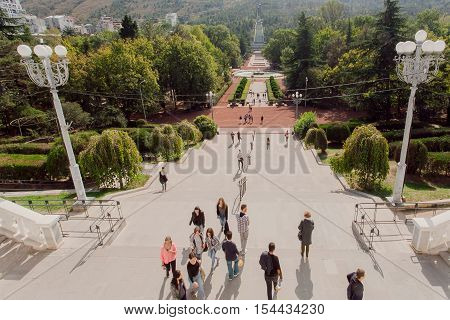 TBILISI, GEORGIA - OCT 16, 2016: People walking in green Vake public park with high trees alley at sunny day on October 16, 2016. Tbilisi has a population of 1.5 million people