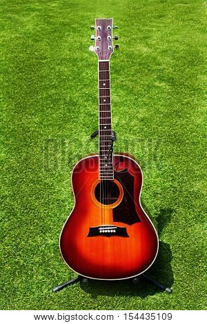 Acoustic guitar on background of green grass. Closeup.