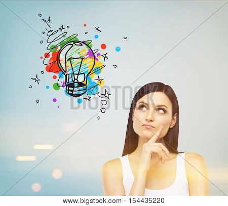 Girl In Tank Top Looking At Light Bulb On Blue Wall, Toned