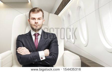 Portrait of businessman sitting in business class of a plane with his arms crossed. Concept of success and luxury. 3d rendering.