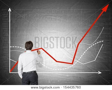 Rear view of businessman in white shirt drawing a graph on chalkboard. Concept of statistician's work