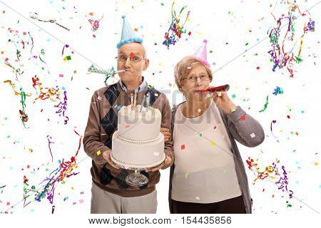 Senior couple with favor horns and party hats celebrating a birthday isolated on white background