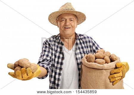 Elderly farmer holding a couple of potatoes and a burlap sack filled with potatoes isolated on white background