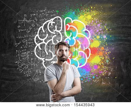 Bearded man in T-shirt standing near giant brain sketch on chalkboard. Concept of logic and senses